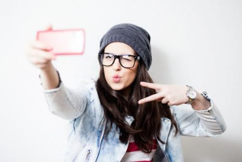 Pretty hipster girl taking selfie and making duck face. Sending kisses and holding peace sign. Instagram